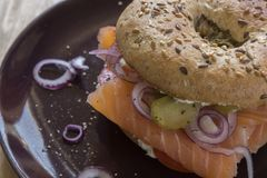 Whole Grain Bagel with salmon, cream cheese, onions and kosher pickle. A whole grain bagel topped with salmon, cream cheese, onions and kosher pickle served on a Stock Images