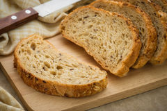 Whole grain bread on chopping board Royalty Free Stock Images