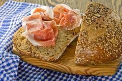 Whole grain bread and prosciutto ham Stock Photos