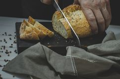 Whole grain bread put on kitchen wood plate with a chef holding gold knife for cut. Fresh bread on table close-up. Fresh bread on the kitchen table The healthy royalty free stock image