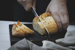 Whole grain bread put on kitchen wood plate with a chef holding gold knife for cut. Fresh bread on table close-up. Fresh bread on the kitchen table The healthy royalty free stock images