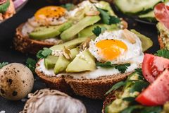 Whole grain bread sandwiches with fried quail egg, avocado, herbs and seeds on black background. Clean eating, healthy vegan breakfast royalty free stock images