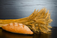 Whole grain bread and a sheaf on a dark background.  Stock Photography