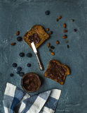Whole grain bread toasts with organic vegan chocolate peanut butter, blueberry, nuts over grunge grey backdrop Royalty Free Stock Photos