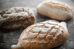 Whole grain breads on the dark wooden background Royalty Free Stock Images