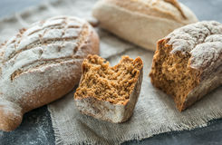 Whole grain breads on the dark wooden background Stock Photography