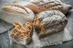 Whole grain breads on the dark wooden background Stock Images
