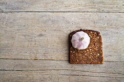 Whole grain brown bread and pungent garlic. Slice of whole grain brown bread and pungent garlic on wooden table royalty free stock photos