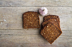 Whole grain brown bread and pungent garlic. Slices of whole grain brown bread and pungent garlic on wooden table royalty free stock image