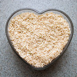 Whole Grain Brown Rice. Dry whole grain brown rice in a heart shaped dish stock images