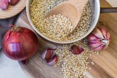 Whole grain brown rice uncooked in pot, onions garlic Royalty Free Stock Photography