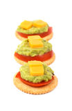 Whole grain crackers with tomato, guacamole and cheese Stock Images