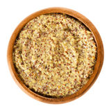 Whole grain Dijon mustard in wooden bowl over white Stock Photos