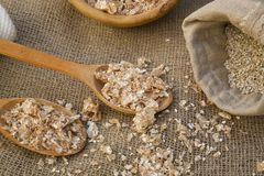 Whole grain flakes. In wooden made spoon on a sackcloth. Textile bag full of barley cereal in the background Stock Images