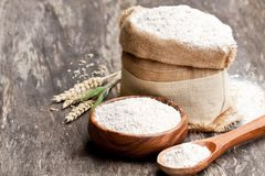 Whole  grain flour in a  wooden bowl and sackcloth bagwith ears. Whole  grain flour in a wooden bowl and sackcloth bagwith ears Royalty Free Stock Photography