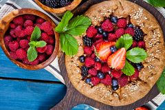 Whole-grain galette with plums and berries on dark background, t. Preparation of whole-grain galette with plums on a white table. top view royalty free stock photos