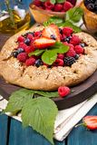 Whole-grain galette with plums and berries on dark background, t. Preparation of whole-grain galette with plums on a white table. top view royalty free stock photography