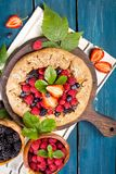 Whole-grain galette with plums and berries on dark background, t. Preparation of whole-grain galette with plums on a white table. top view stock image