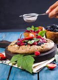 Whole-grain galette with plums and berries on dark background, t. Preparation of whole-grain galette with plums on a white table. top view stock photo
