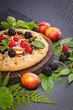 Whole-grain galette with plums and berries on dark background, t. Preparation of whole-grain galette with plums on a white table. top view royalty free stock images