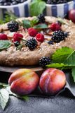 Whole-grain galette with plums and berries on dark background, t. Preparation of whole-grain galette with plums on a white table. top view stock photos