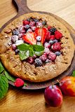 Whole-grain galette with plums and berries on dark background, t. Preparation of whole-grain galette with plums on a white table. top view stock photography