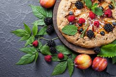 Whole-grain galette with plums and berries on dark background, t. Preparation of whole-grain galette with plums on a white table. top view stock images