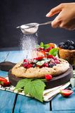 Whole-grain galette with plums and berries on dark background, t. Preparation of whole-grain galette with plums on a white table. top view royalty free stock photo
