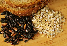 Whole grain goodness. Close up image of whole wheat bread, steel cut oats, and black rice on wood cutting board Stock Photo