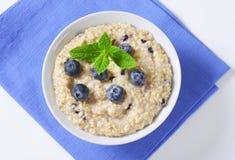 Whole grain oat porridge. Bowl of whole grain oat porridge with blueberries Stock Photos