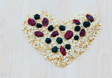 Whole grain oats with dried cranberries and blueberries in heart Royalty Free Stock Photography