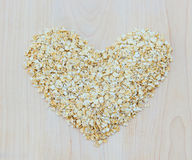 Whole grain oats in heart shape on wooden board Royalty Free Stock Photography