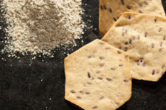 Whole grain organic cracker and flour on the black Stock Image