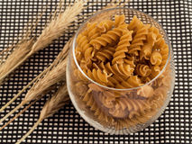Whole grain pasta. Dose of whole grain pasta in glass with wheat Royalty Free Stock Images