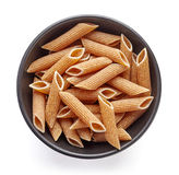 Whole grain pasta in bowl isolated on white, from above Stock Images