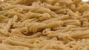 Pasta Whole Grain Fill. Whole grain pasta falling on white background and filling the screen in slow motion stock footage