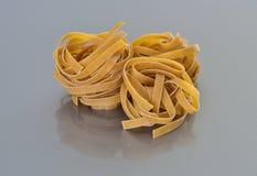 Whole grain pasta nests. Italian whole grain pasta nests on grey background closeup shot royalty free stock photo