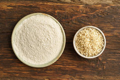 Whole-grain rice and rice flour. In small bowls stock image