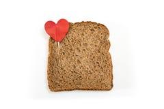 Whole grain sandwich bread slice with heart pin, on white background. Whole grain sandwich bread slice with heart pin, on white background Royalty Free Stock Image