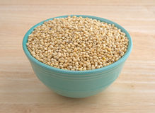 Whole grain sorghum seeds in a bowl on a table. A small bowl filled with whole grain organic sorghum seeds on a wood table top Stock Photo