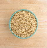 Whole grain sorghum seeds in a bowl on a table. Top view of a small bowl filled with whole grain organic sorghum seeds on a wood table top Royalty Free Stock Photos