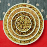 Whole grain target. Whole grains arranged in concentric white bowls on red and blue decorated papers Stock Image