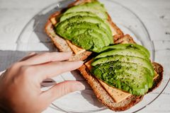 Whole grain toasts with avocado, cheese and herbs. A useful delicious breakfast. stock photos