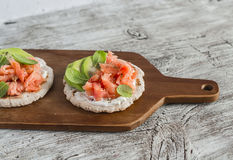 Whole grain tortilla with avocado and salmon, served on a wooden board, bright wooden surface. Royalty Free Stock Image