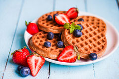 Whole grain waffles with berries on blue wooden background Royalty Free Stock Images