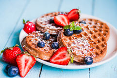 Whole grain waffles with berries on blue wooden background Stock Photo