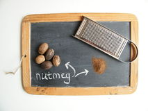 Nutmeg. Whole and grated nutmeg with grater on a blackboard Royalty Free Stock Image