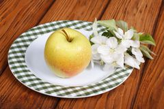 Whole green apple with flowers on a white plate Royalty Free Stock Photography