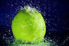 Whole green apple with stopped motion water drops Stock Photography