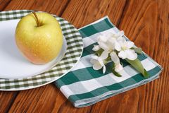 The whole green apple on a white plate Royalty Free Stock Photos